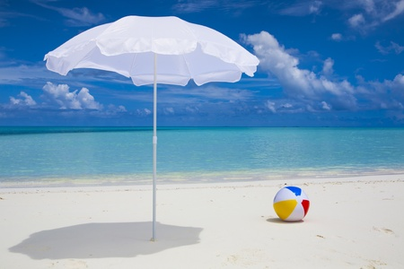ombrellone spiaggia: solitario ombrellone bianco e una palla in spiaggia con un cielo azzurro e un mare turchese