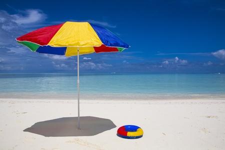 een rood, geel, blauw en groene parasol en een zwemmende ring op het strand met een turquoise zee