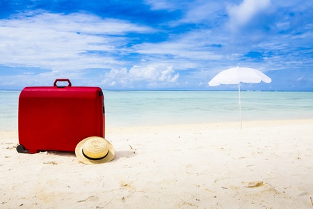 red suitcase, straw sun hat and white sunshade at a beach with a blue ky and some clouds Standard-Bild