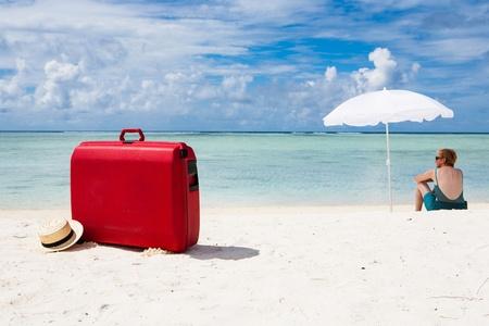 mujer con maleta: Mujer con la maleta roja sentado bajo una sombrilla blanca en la playa