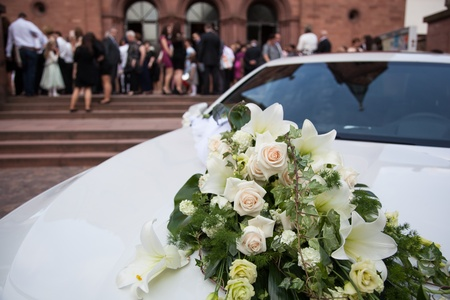 white limousine with a flower bouquet and guests of a wedding ceremony in front of a church photo