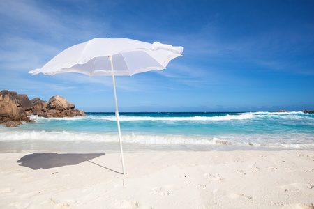 white sunshade at the tropical beach of La Digue, Seychelles, with granite rocks  and blue sky  Stok Fotoğraf