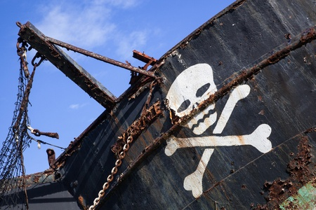 white skull with crossed bones on a rusty old black pirate ship