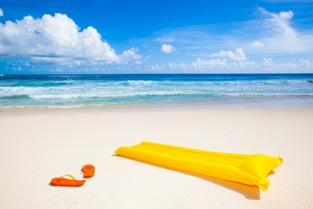 yellow air mattress and orange flip-flops at a beautiful beach with a turquoise sea
