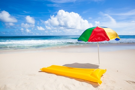 colorful sunshade and yellow air mattress at a beautiful beach with a turquoise sea