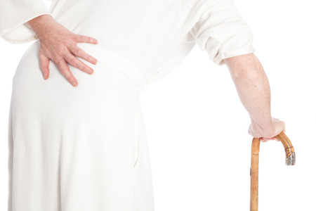 invalid old woman in a white bath robe with pain in the back walking with a stick and pressing one hand against her aching back