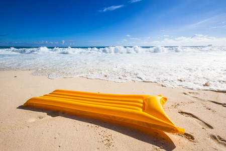yellow air mattress in the sand of a tropical beach with a turquoise sea and blue sky in the background Standard-Bild