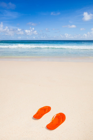 travel background with a pair of orange flip-flops in the sand of a besutiful beach, blue sky and turquoise sea