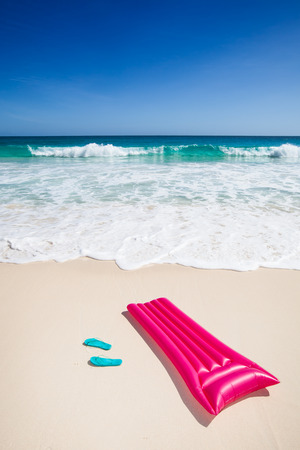 travel background with pink air mattress and green flip-flops at a beach with a turquoise sea and blue sky