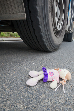 wheels of a truck and a doll on the asphalt after an accident with a little child Stok Fotoğraf