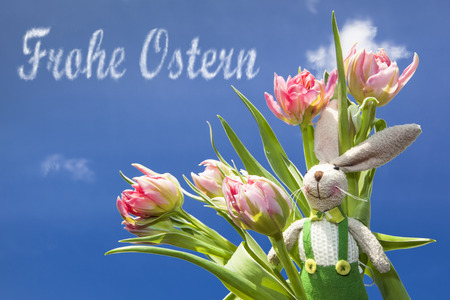 ostern: easter bunny in green pants in front of pink tulips and the wish Frohe Ostern is written with cloud script in the blue sky