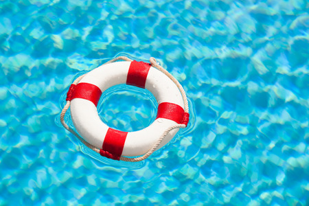 red and white life buoy or life-saver floating in the blue water of a swimming pool