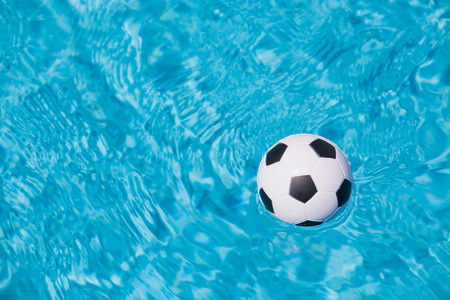 sport background of a little plastic football floating in the blue water of a swimming pool