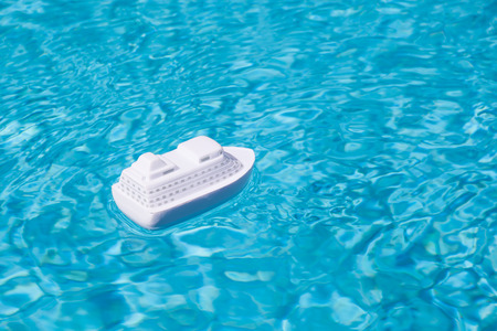 travel background of a little white model passenger ship cruising in the blue water of a swimming pool