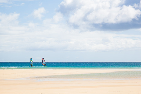 travel background with a white and lonely beach under a blue sky with some clouds and two windsurfer, playa de Sotavento, Fuerteventura, canary islands, Spain, Europe photo