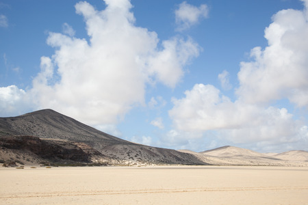blue sky with some clouds over dunes and hills at the white and lonely beach of playa de Sotavento de Janida, Fuerteventura, canary islands, Spain, Europe photo