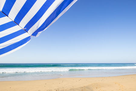 travel background with a blue and white sunshade at an endless white beach with a blue sky and a turquoise sea,  Playa de las Pilas, Fuerteventura, canary islands, Spain, Europe Stok Fotoğraf