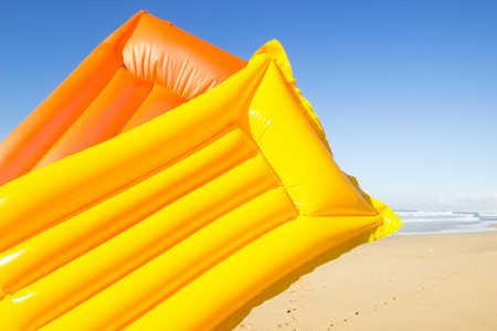 travel background with a yellow and orange air mattress at an endless white beach with a blue sky and a turquoise sea,  Playa de las Pilas, Fuerteventura, canary islands, Spain, Europe
