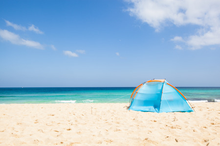 camping with a tent at a lonesome beach with a turquoise sea and blue sky in the background, Fuerteventura, Canary Islands, Spain, Europe