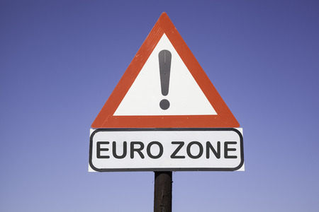 eurozone: White road warning triangle with black  exclamation point and red frame on  a wooden mast in front of a blue sky  A second rectangular sign warns in english about Eurozone