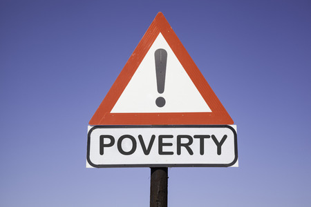 White road warning triangle with black  exclamation point and red frame on  a wooden mast in front of a blue sky  A second rectangular sign warns in english about poverty