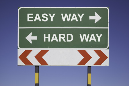 green traffic sign in front of a blue sky, horizontal arrows showing two directions and a red white road warning post  Business concept for activity and decision  Choose easy or hard way photo