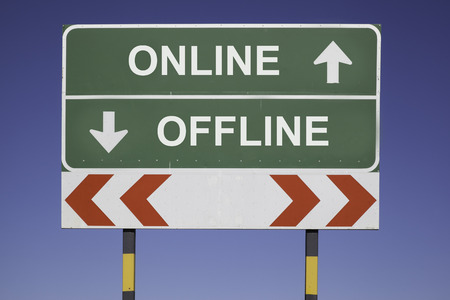 informed: green traffic sign in front of a blue sky, horizontal arrows showing two directions and a red white road warning post  Business concept for information and computing  Be online not offline  Stock Photo