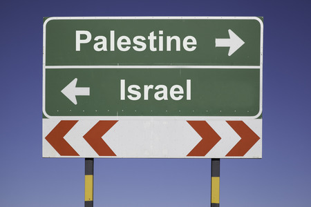 green traffic sign in front of a blue sky, horizontal arrows showing two directions and a red white road warning post  Business concept for the relations or conflicts between Palestine, Israel photo