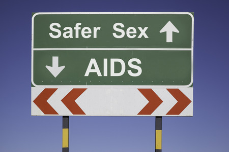 sex traffic: green traffic sign in front of a blue sky, horizontal arrows showing two directions and a red white road warning post  Health concept for safer sex  Use Condom or get AIDS Stock Photo