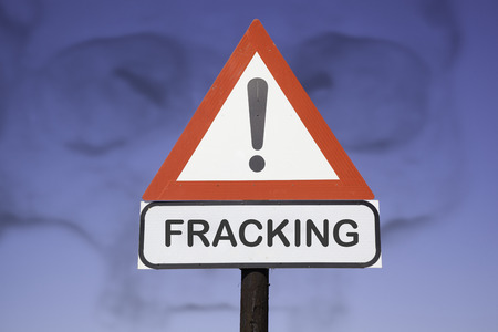 exitus: White road warning triangle with black  exclamation point and red frame on  a wooden mast in front of a blue sky. A second rectangular sign warns in english about  fracking Stock Photo