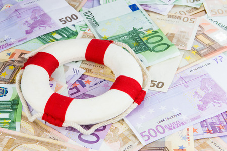 red and white life-saver on Euro banknotes, concept for Euro crisis, cut in interest rates photo