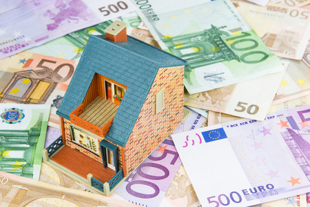 house prices: model of a toy house placed on Euro banknotes. Concept for real estate costs, prices, buy or rent a house, hypothecary credit, interest