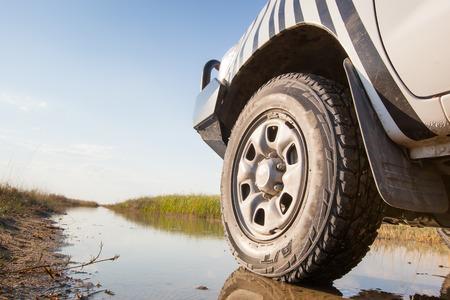 volante de un coche 4x4 blanco a la izquierda en una pista mojada en el santuario de aves de pantano de Nata, Botswana, África
