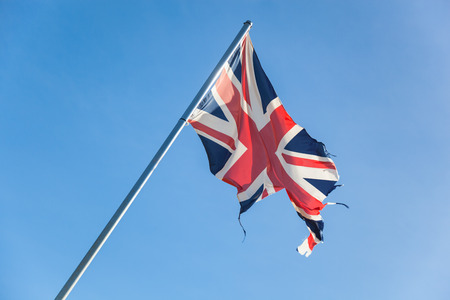 tattered british flag in front of the blue sky. Concept for separatism or collapse of Great Britain