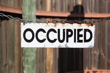 occupied: old grungy white metal sign with word occupied in black letters hanging at a chain in front of a wooden wall, concept for not available things
