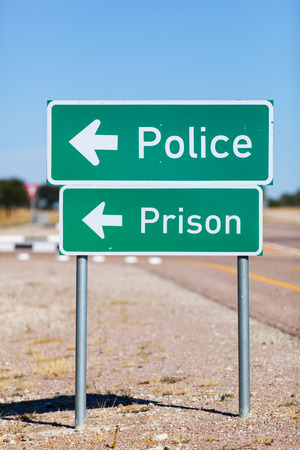 constabulary: two green metal at a tar road signs showing the way to police and prison concept for the result of crime
