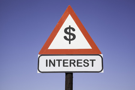white interest rate: White road warning triangle with black  exclamation point and red frame on  a wooden mast in front of a blue sky. A second rectangular sign warns in english about Dollar interest rate