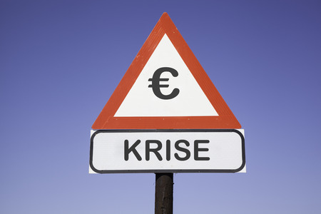 german mark: White road warning triangle with black  exclamation point and red frame on  a wooden mast in front of a blue sky. A second rectangular sign warns in german about  Euro crisis