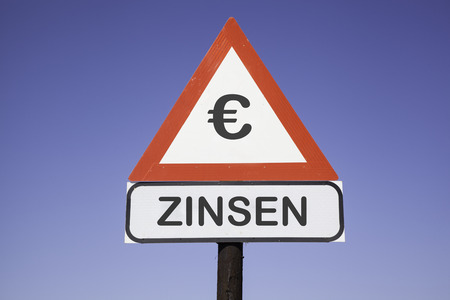 white interest rate: White road warning triangle with black  exclamation point and red frame on  a wooden mast in front of a blue sky. A second rectangular sign warns in german about interest rate