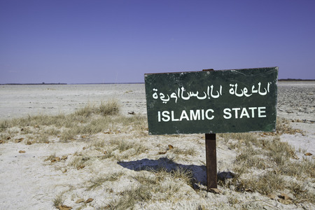 green sign with the word islamic state in arabic and english language standing in the white sand of the desert. Standard-Bild