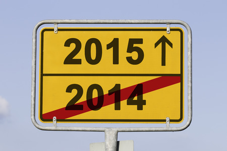 turns of the year: yellow traffic sign showing the end of the year 2014, which is crossed,  and an arrow shows that the the year 2015 is ahead. concept for fiscal year change.