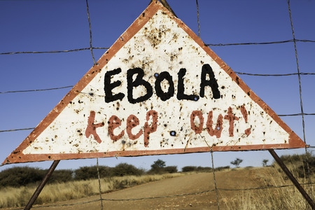 exitus: old rusty warning triangle at a fence in Africa  with the words Ebola keep out Stock Photo