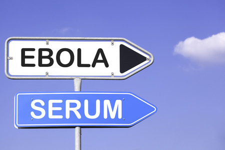 exitus: blue sky behind two white and blue road signs  on a metal mast with arrows to the right hand side showing the way to Ebola Serum Stock Photo