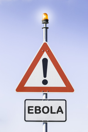 exitus: White road triangle with a black exclamation point and a red frame on a metal mast with a orange warning light on top in front of a blue sky. A second rectangular sign warns in english about Ebola