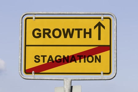 Blue sky behind a yellow city limit or place name sign informing with an arrow that you are on the way to growth and leaving stagnation Stock Photo