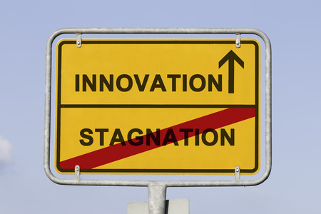 Blue sky behind a yellow city limit or place name sign informing with an arrow that you are on the way to innovation and leaving stagnation Stock Photo