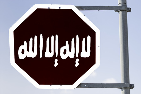 testimony: black stop sign which looks like the banner of islamic state in the center is written  shahada in arabic latters, which means testimony. Concept for: Stop the IS and stop entering Islamic State