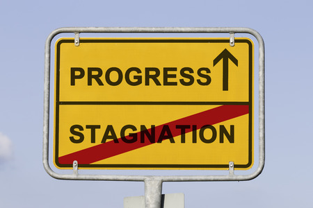 stagnate: Blue sky behind a yellow city limit or place name sign informing with an arrow that you are on the way to progress and leaving stagnation