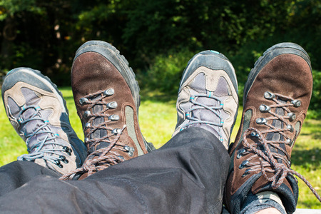 rambling: resting legs with two pairs of brown and grey hiking boots after rambling in the forest Stock Photo