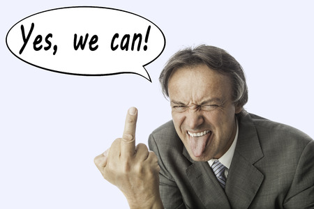 business for the middle: elder mad business man in a grey suite poking one´s tongue and showing his middle finger. In a speech balloon are written the words: Yes, we can. Concept for anger, stress and bad service. Stock Photo